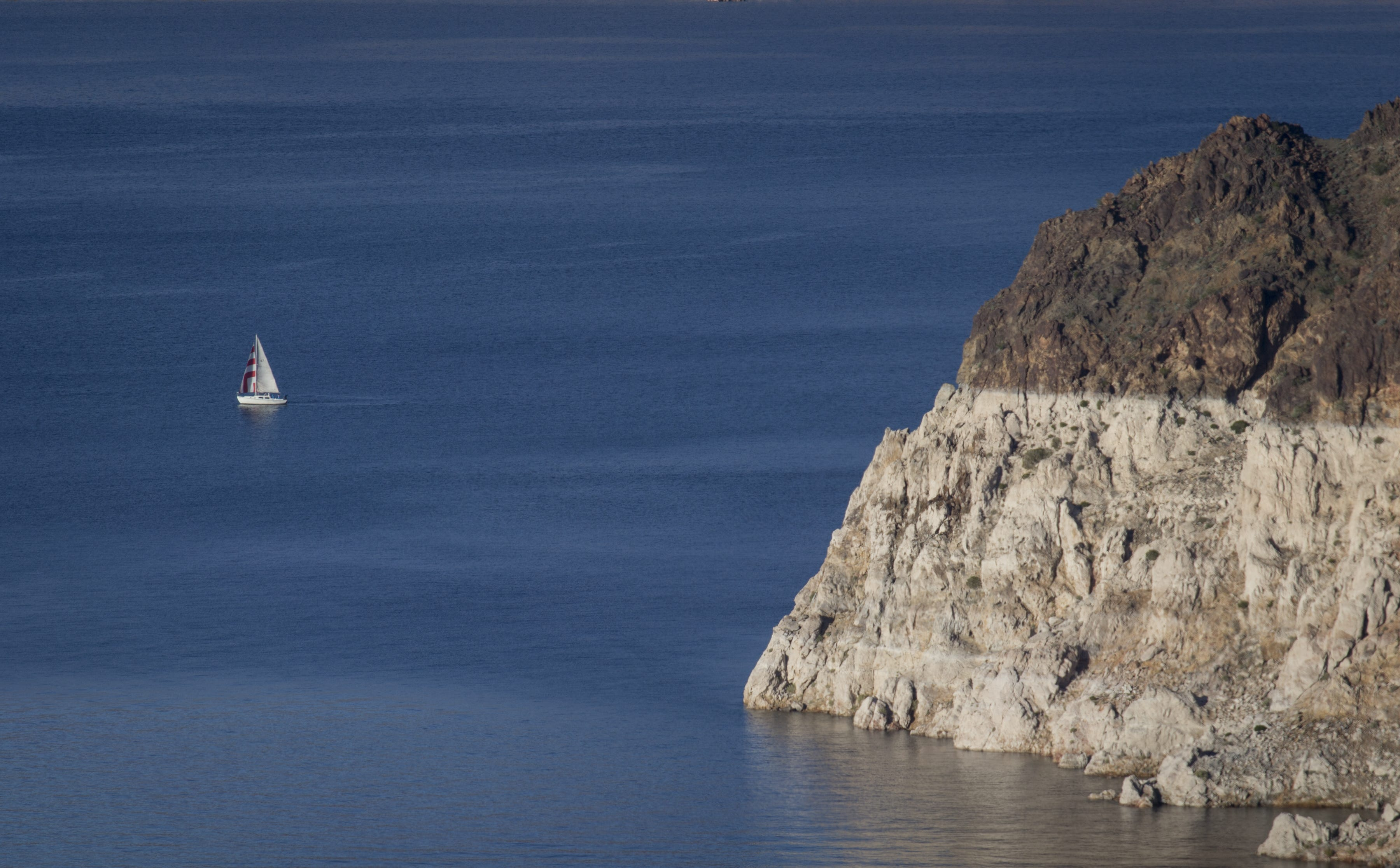 """A sailboat cruises in the Lake Mead National Recreation Area near the Arizona-Nevada border. A high-water mark, or """"bathtub ring,"""" is visible on the shoreline."""