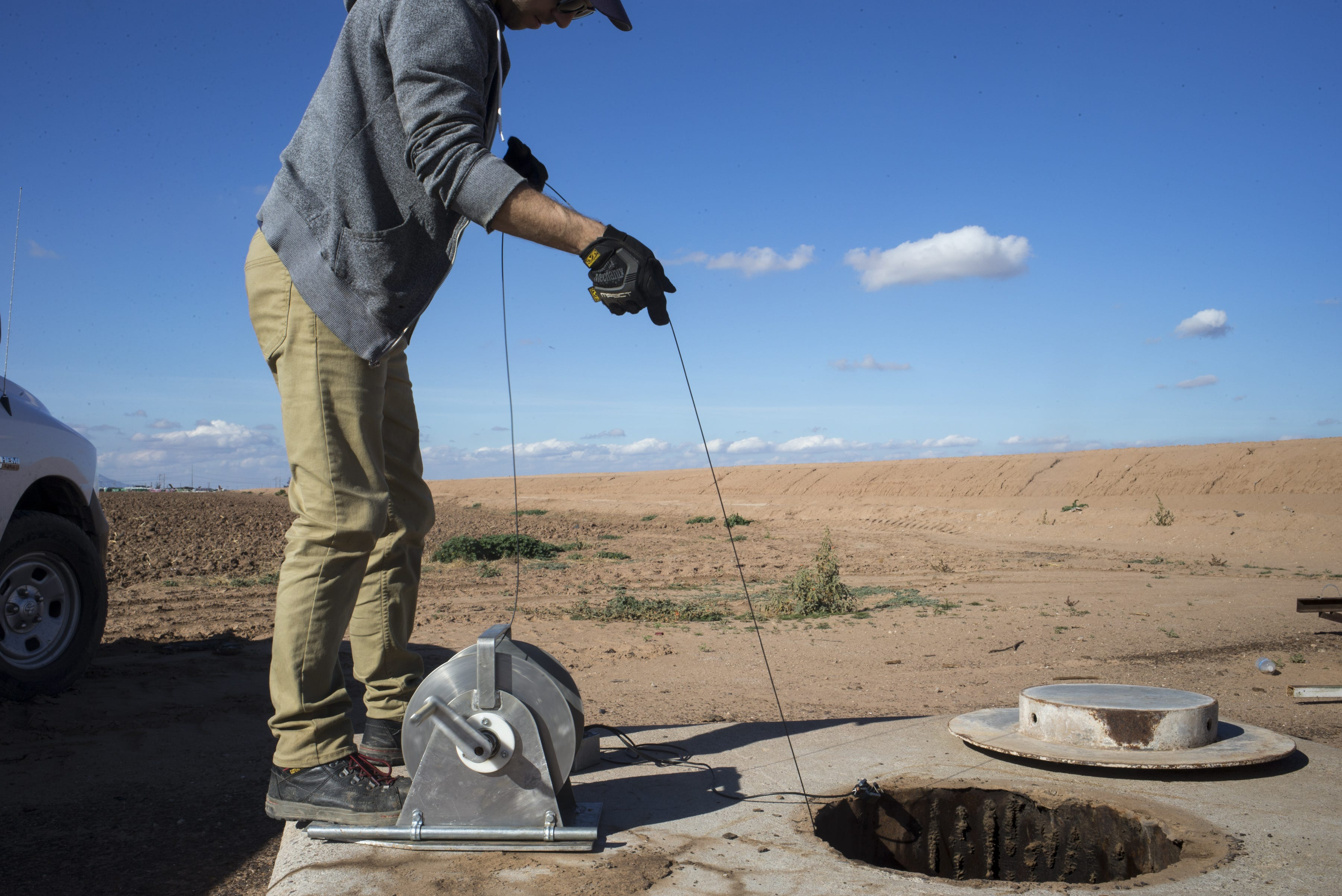 Scott Stuk of the Arizona Department of Water Resources drops a probe down an unused well south of Maricopa. The water depth was 280 feet.