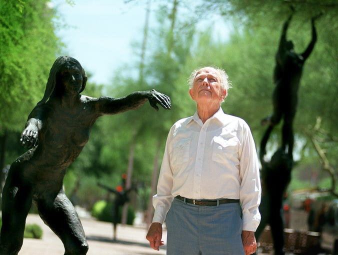 In this 2001 photo, sculptor John Henry Waddell stands with the figures he created  in front of the Herberger Theater Center in Phoenix. Waddell died on Nov. 27, 2019.