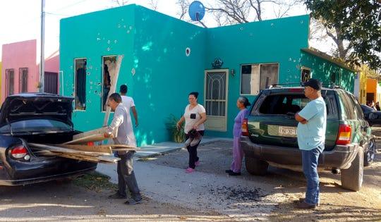 Los residentes se paran frente a una casa llena de agujeros de bala después de un tiroteo entre las fuerzas de seguridad mexicanas y presuntos pistoleros del cártel, en Villa Unión, México, el sábado 30 de noviembre de 2019.