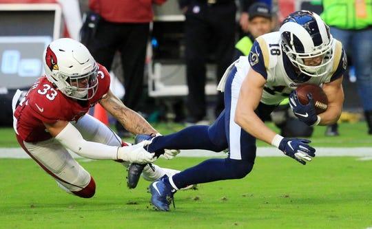 El esquinero de los Arizona Cardinals Byron Murphy Jr. (izq) detiene al receptor abierto de los Rams de Los Ángeles Cooper Kupp (R) después de una recepción de pase durante el partido de fútbol americano de la NFL entre los Rams de Los Ángeles y los Cardenales de Arizona en Glendale, Arizona, EE. UU.