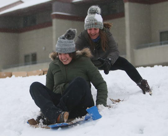 Marist students, Amelia Nick gives Melissa Fletcher a push to get down the hill on her improvised sled during Monday's snow storm on December 2, 2019.