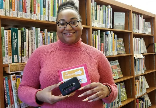 Martin Library Information Services Coordinator LaChaun Freeland holds one of the 15 mobile hotspots available to borrow at Martin Library and Collinsville Community Library now through February as part of a pilot project with T-Mobile.