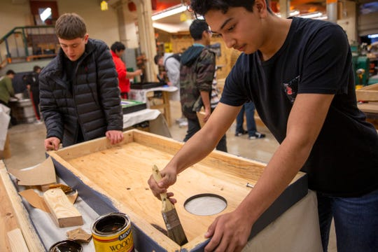 McKay sophomores Elijah Gust and Pablo Barocio paint a corn hole board that will be donated to a P.E. class during Woods II at McKay High School in Salem on Nov. 21.