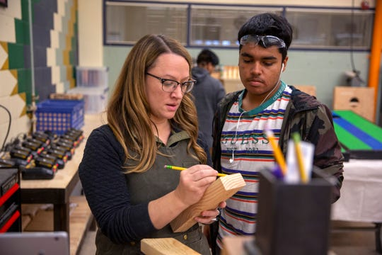Woodshop and construction teacher Michelle Zielinski helps a student measure supplies during Woods II at McKay High School in Salem on Nov. 21.