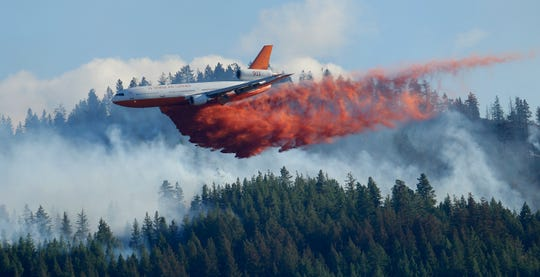 In this Aug. 21, 2015 file photo, a tanker airplane drops fire retardant on a wildfire burning near Twisp, Wash.