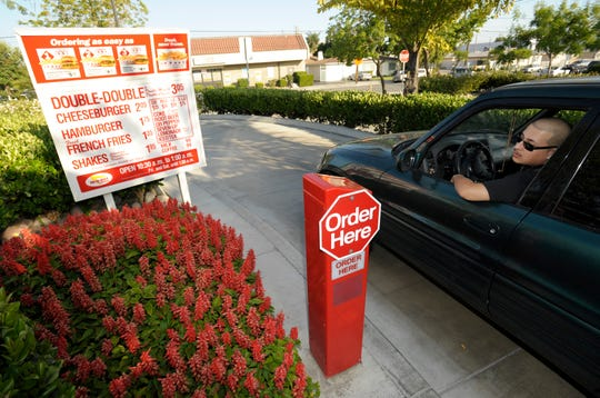 In this June 8, 2010 photo, Paul Rodriguez orders in the drive-through lane at In-N-Out Burger in Baldwin Park, Calif.