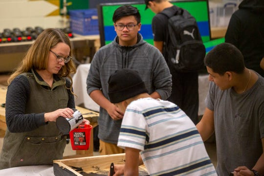 Woodshop and construction teacher Michelle Zielinski pours paint for her students during Woods II at McKay High School in Salem on Nov. 21.