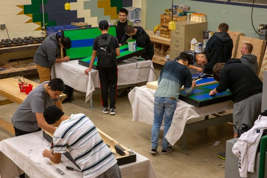 Students paint cornhole boards that will be donated to a P.E. class during Woods II at McKay High School in Salem on Nov. 21.