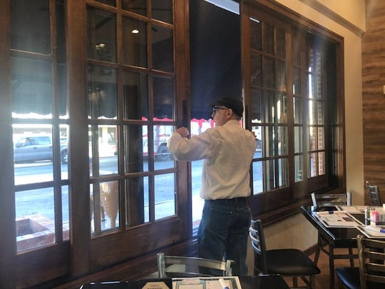 Owner John Fuentes opens up new sliding windows at Fuentes Cafe, 101 S. Chadbourne St., on Dec. 2, 2019.