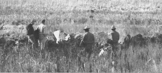 Local law enforcement and then-Gov. Bill Janklow (left) inspect the wreckage of a plane that crashed near Mina in 1999.