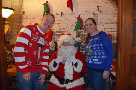 """Santa (Nigel Bembry) gives a thumbs up to """"ugly Christmas sweaters"""" worn by Nicholas Lewis and Jennifer Cooper Lewis at last year's Ugly Christmas Sweater Party for Rescue One. This year's party is set for Dec. 6."""