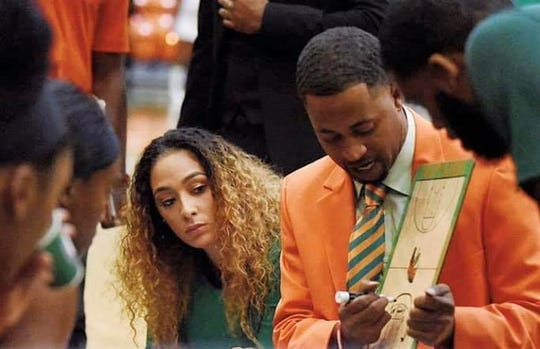 FAMU women's basketball head coach Kevin Lynum draws up a play during a timeout.