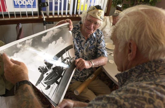 In this file image from Dec. 2, 2001, Pearl Harbor survivor Ross Witham, 84, of Stuart, left,  shows fellow survivor Pat Librie, 80, of Sebastian a photo of the JRS-1 he served on as a crew member of during World War II.  The two were taking part in a Pearl Harbor veterans get-together at Johnny's Corner in Port St. Lucie.