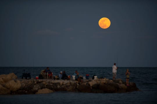 May's full moon, nicknamed the flower moon, rises over the horizon as people fishing off the jetty watch Saturday, May 18, 2019, at South Jetty Park in Fort Pierce. The last full moon of 2019, and the decade, will rise at 12:12 a.m. Dec. 12.