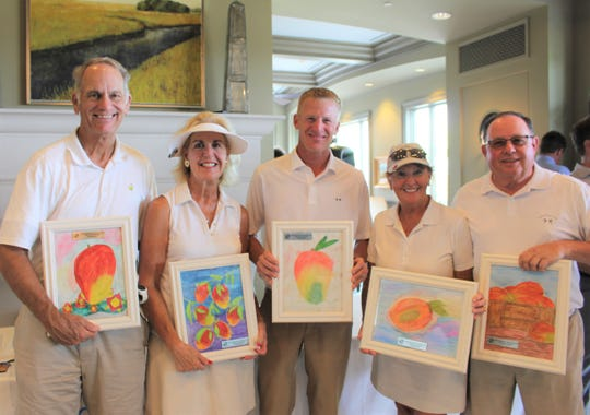 The winning team of the Boys & Girls Clubs of Indian River County Pro Am Golf Tournament, from left, John Hendricks, Maureen Hendricks, Jonas DeWitte (professional), Patsy Lees and Steve Lees with their prizes of custom artwork created by Sebastian Boys & Girls Club members.