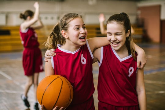 Teenage girls embracing after basketball ball game