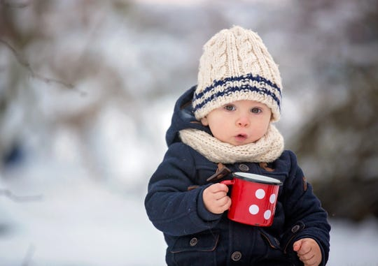 A young child drinking from a mug in the snow