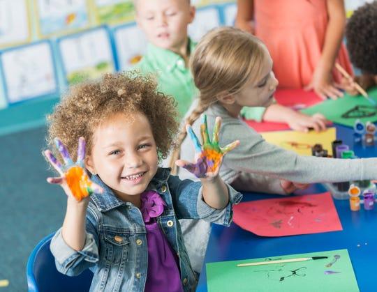 A little girl in art class in kindergarten.