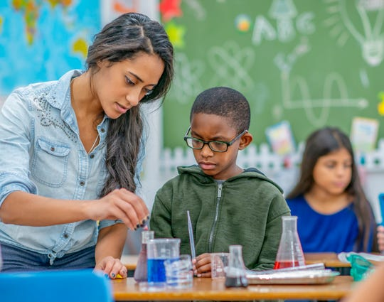 A youn teacher helps a boy in her class to conduct a chemistry experiment.