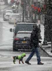 A dog owner has his dog well prepared for the first winter storm of the season as they cross Main Street in Tarrytown Dec. 2, 2019. Up to seven inches of snow is forecasted for the region as the snow is predicted to fall through part of Tuesday.