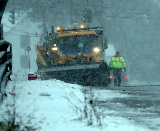 A snowplow driver checks his truck on Rt. 304 in Bardonia as snow falls Dec. 2, 2019.