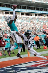 Miami Dolphins wide receiver DeVante Parker (11) catches a pass for a touchdown as Philadelphia Eagles cornerback Jalen Mills (31) defends during the second half Sunday.