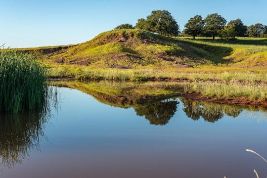 A rolling hill is seen by the water at the Little Wichita River Ranch.