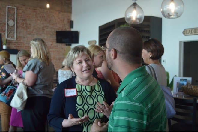 Ruth Jones, Impact 100 board member, discusses the organization's grant process at a meet and greet.