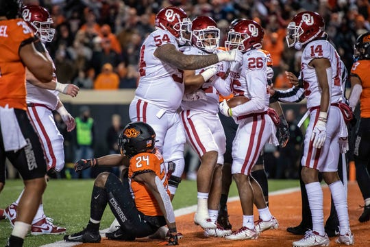 Oklahoma running back Kennedy Brooks (26) celebrates with teammates after scoring a touchdown against Oklahoma State during the second half at Boone Pickens Stadium.
