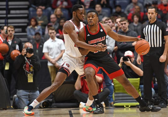 Louisville center Steven Enoch dribbles the ball against the defense of Western Kentucky center Charles Bassey during the first half at Bridgestone Arena.