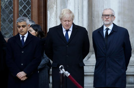 ritain's Prime Minister Boris Johnson, center, Labour Party leader Jeremy Corbyn, right, and Mayor of London Sadiq Khan take part in a vigil at Guildhall Yard in London, Monday Dec. 2, 2019.