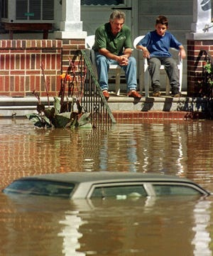 A man and boy sit on their front porch surrounded by water and a  submerged car in their front yard in Lodi, N.J., Friday, Sept. 17, 1999. Lodi is one of the towns around the state that was inundated by flood waters from Hurricane Floyd. (AP Photo/Mike Derer)