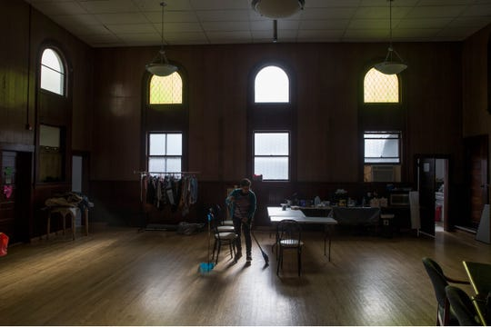 Pastor Marisol Ferrer Malloy cleans up the area used as a Code Blue warming center at the Community Mission Center in Long Branch. It was formerly the First Reformed Church.