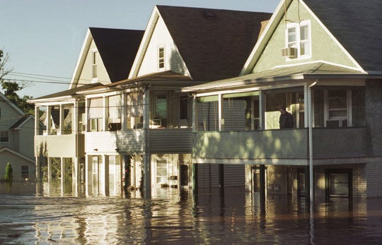 A man surveys his flooded neighborhood in Bound Brook, N.J., from his second floor porch in this  Sept. 17, 1999 photo. The remnants of Hurricane Floyd that flooded New Jersey last Sept., killed four people, caused more than $500 million in damage and ruined thousands of homes and businesses. (AP Photo/Mike Derer)