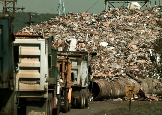 Trucks line up  to unload at  a dump site  for flood debris in Bridgewater, N.J. Friday Sept. 24, 1999. Flooding  from Hurricane Floyd has generated mounds of flood damaged belongings.  (AP Photo/Daniel Hulshizer)