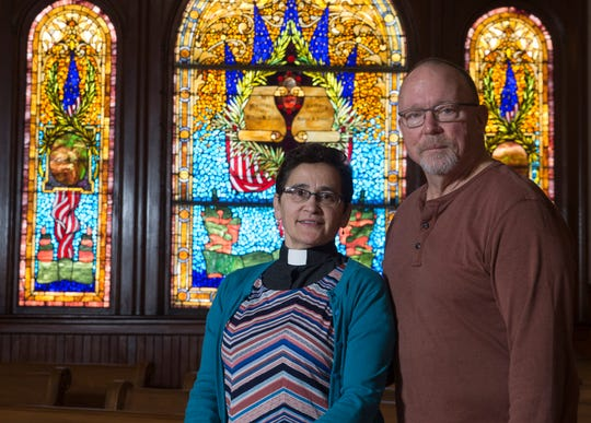 Pastor Marisol Ferrer Malloy and her husband Paul Malloy stand by the historic McKinley Window, a stained glass window dedicated to the former president at the Community Mission Center (formerly First Reformed Church) in Long Branch.