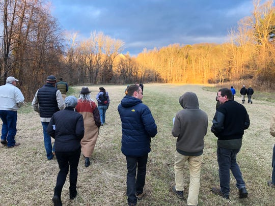 Concerned neighbors and developers walk the site of the proposed Crossroads at West Asheville, an 802-unit apartment complex that will include retail and commercial development. The site on South Bear Creek Road used to be a dairy farm.