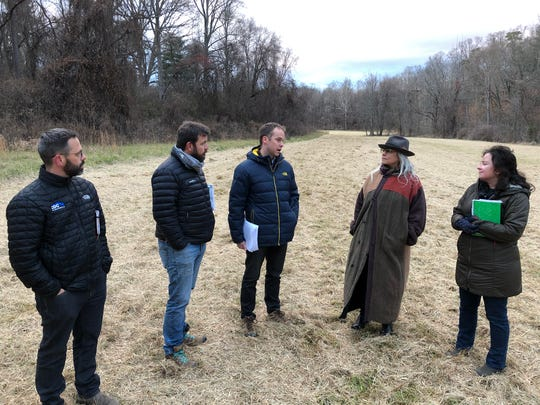 From left, engineer Chris Day, Asheville Greenworks Director of Operations Eric Bradford, developer A.J. Klenk, and neighbors Stephanie Crawford and Kate Millar discuss the proposed Crossroads at West Asheville project while walking the site Dec. 2. The project, to be built on 68 acres on a former dairy farm, runs near Hominy Creek, to the right.