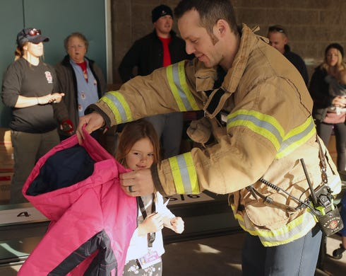 Bremerton Firefighter Jake Bower helps Iris Haag, 7, try on her new jacket during the Kitsap Fire Fighters Benevolent Fund annual Coats for Kids event at Crownhill Elementary School in Bremerton on Monday, December 2, 2019.