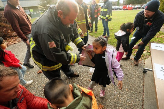 Retired Central Kitsap firefighter Henry Henneman helps kindergartener Glendy Ramos-Pablo try on a new coat during the Kitsap Fire Fighters Benevolent Fund's annual Coats for Kids event at Armin Jahr in Bremerton on Tuesday.