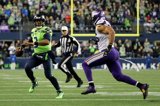 Seattle Seahawks quarterback Russell Wilson (3) scrambles as Minnesota Vikings' Anthony Barr approaches during the first half of an NFL football game, Monday, Dec. 2, 2019, in Seattle.