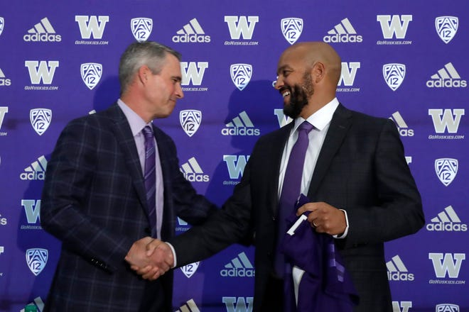 Washington NCAA college football head coach Chris Petersen, left, shakes hands with defensive coordinator Jimmy Lake following a news conference about Lake taking over the head coaching position, Tuesday, Dec. 3, 2019, in Seattle. Petersen unexpectedly resigned on Monday, a shocking announcement with the Huskies coming off a 7-5 regular season and bound for a sixth straight bowl game under his leadership. Petersen will coach Washington in a bowl game, his final game in charge. (AP Photo/Elaine Thompson)