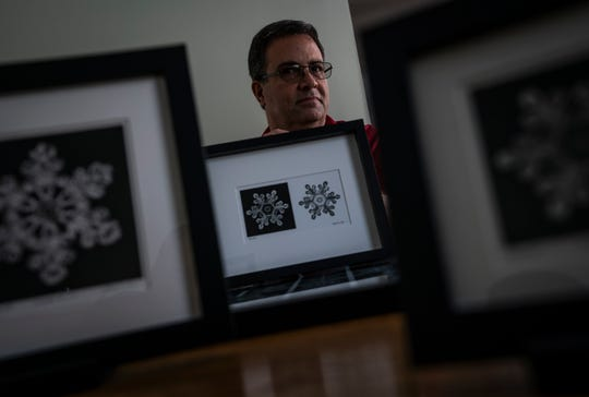 Stuart Hall of Jericho shows a print of the first snowflake he ever photographed in March 2007. Since then, he's photographed more than 27,000 snowflakes, carrying on a legacy started by Wilson 'Snowflake' Bentley in 1885 less than a mile from Hall's home.