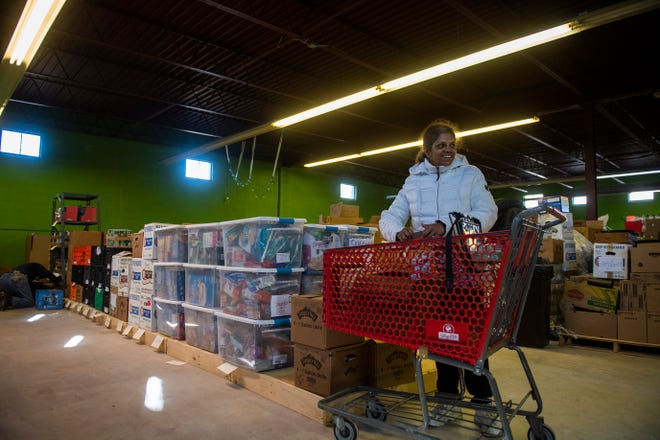 Vidya Nayak loads a shopping cart as volunteers work inside the new food pantry location in Cherry Hill Tuesday, Dec. 3, 2019.