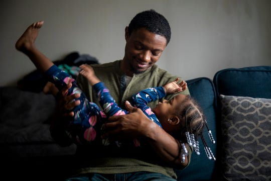 Marine Corps veteran LeRon Davis holds his daughter Ahnalia, 2,  in their apartment in Mt. Airy on Thursday, November 21, 2019.