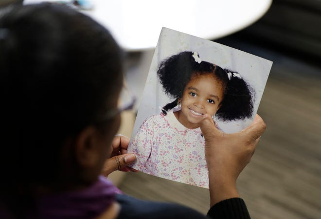 In this Oct. 29, 2019, photo, Donnesha Cooper touches a photo of her daughter, Alianna DeFreeze, in Cleveland. Her daughter's murder and the murder of Reagan Tokes had a lot in common. Yet only one victim got a law with her name on it, Tokes, who was white.