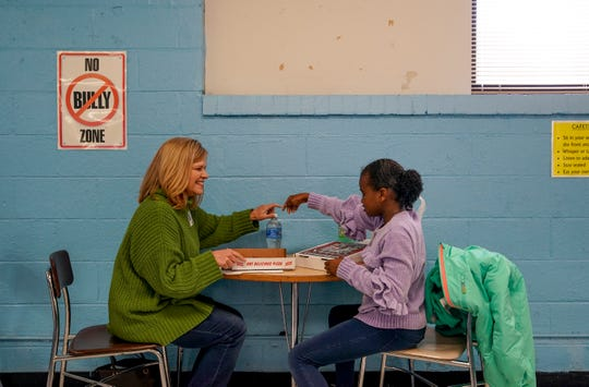 Susan Dickonson, left, and Nevaeh Tolbert, 9, right, share lunch in the school cafeteria at Burt Elementary School in Clarksville, Tenn., on Thursday, Nov. 14, 2019.