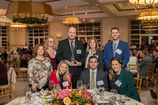 The New Jersey Bankers Association has selected Unity Bank Staff Accountant Jason Murray as a New Leader in Banking. He is pictured with his award with Unity Bank employees. From left to right standing are Assistant Controller Denise Stull, Wire Transfer Specialist Catherine Holland, Controller Laurie Cook and Staff Accountant Scott Anderson. Seated from left are Senior Staff Accountant Delphine Marini, Staff Accountant Lucas Approvato and Finance Department Supervisor Amy Downes.