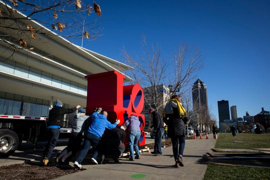 "The installation team from the Des Moines Art Center installs Robert Indiana's ""LOVE"" sculpture on its new base in the Sculpture Park on Tuesday, Dec. 3, 2019, in Des Moines. The sculpture had been taken down temporarily as a new pedestal was built for it."